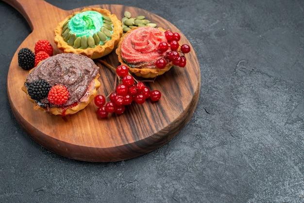 Vista frontal deliciosos pasteles cremosos con bayas sobre fondo oscuro
