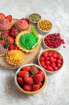 Vista frontal deliciosos pasteles cremosos con frutas sobre fondo blanco.