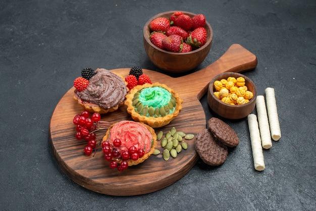 Vista frontal deliciosos pasteles cremosos con frutas sobre fondo oscuro
