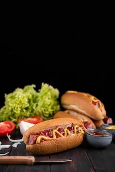 Vista frontal de deliciosos perros calientes con salsa de tomate y mostaza