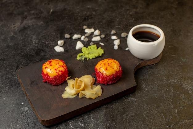 Vista frontal de deliciosos rollos de pescado de comida de sushi con pescado y arroz junto con salsa en la pared gris