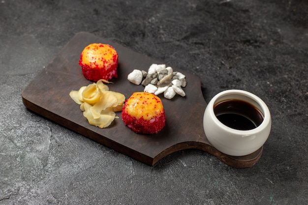 Vista frontal de deliciosos rollos de pescado de sushi con pescado y arroz junto con salsa en la pared gris