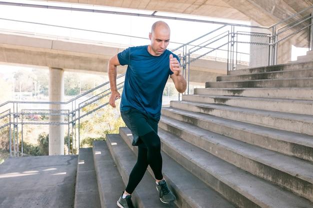 Vista frontal del deportista corredor masculino corriendo por las escaleras de la ciudad para trotar