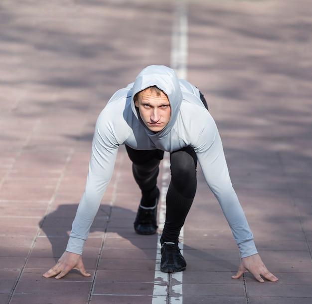 Vista frontal deportivo hombre preparándose para correr