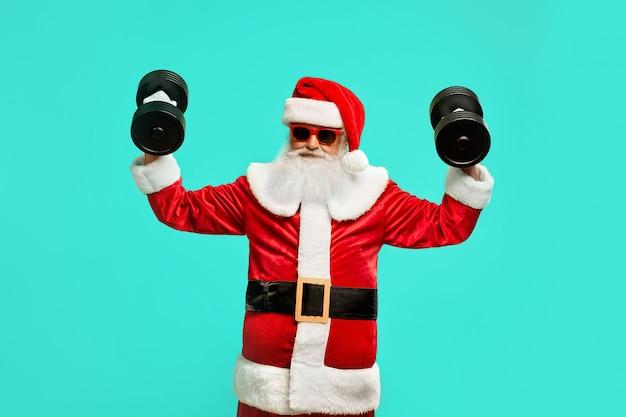Vista frontal del deportivo santa claus sosteniendo dumbbels. retrato aislado del hombre mayor divertido en traje de navidad y gafas de sol posando