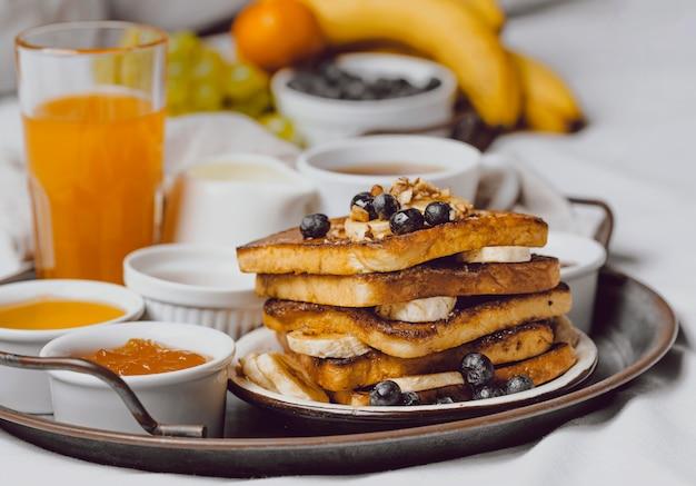 Vista frontal del desayuno en la cama con tostadas y plátano