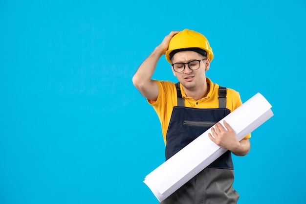 Vista frontal destacó constructor masculino en uniforme con plan de papel en azul
