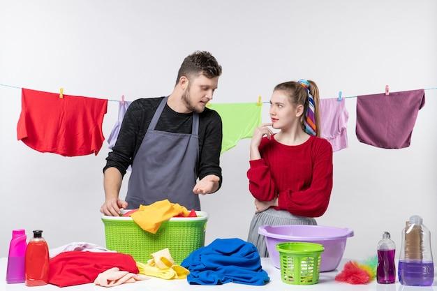 Vista frontal del día de la limpieza, el hombre y la esposa de pie detrás de la mesa cestas de lavandería y lavando cosas en la mesa con una cuerda