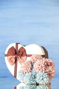 Vista frontal del día de san valentín presente con flores sobre fondo azul claro color amor pasión pareja sentimiento familia belleza corazones