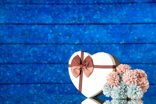 Vista frontal del día de san valentín presente con flores sobre un fondo azul matrimonio familiar sentimiento amor belleza color pasión amante