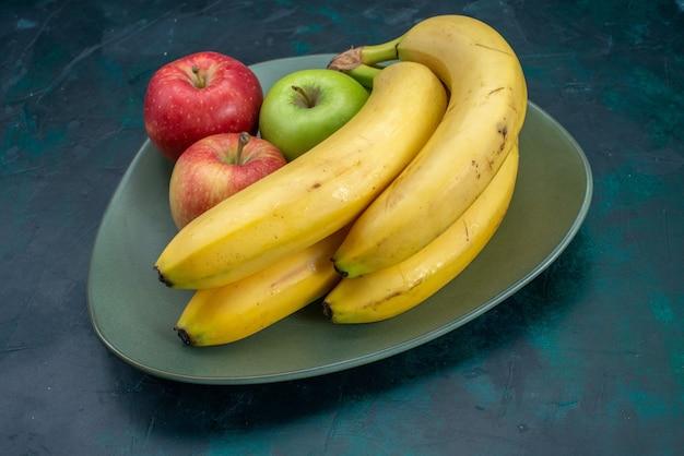 Vista frontal diferente composición de frutas manzanas y plátanos en el escritorio azul oscuro fruta tropical exótica suave fresca