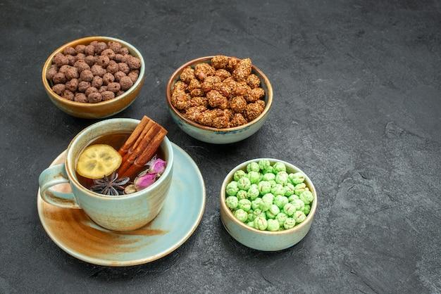 Vista frontal de diferentes caramelos dulces con taza de té en el espacio gris