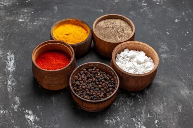 Vista frontal de diferentes condimentos dentro de pequeñas ollas en la mesa oscura pimienta color especia