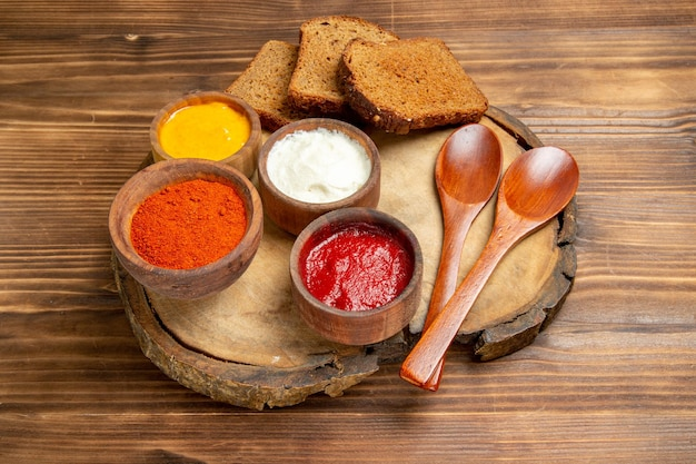 Vista frontal diferentes condimentos con hogazas de pan oscuro en un escritorio marrón condimento picante de pan