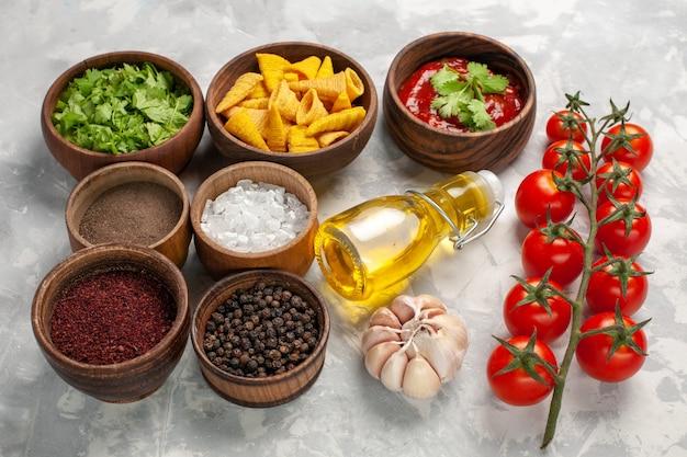 Vista frontal diferentes condimentos con tomates cherry y aceite en superficie blanca producto ingrediente vegetal picante picante
