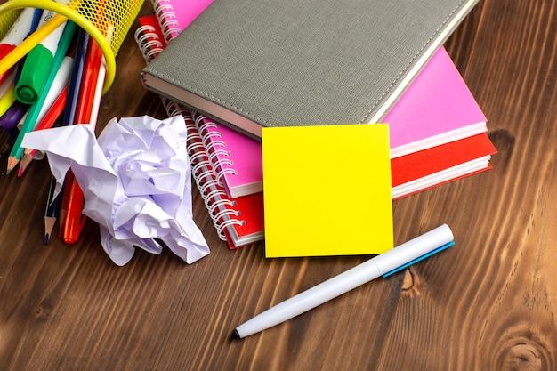 Vista frontal de diferentes cuadernos coloridos sobre la superficie marrón
