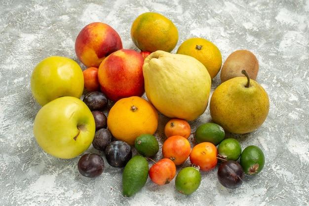 Vista frontal de diferentes frutas de composición de frutas frescas en el espacio en blanco