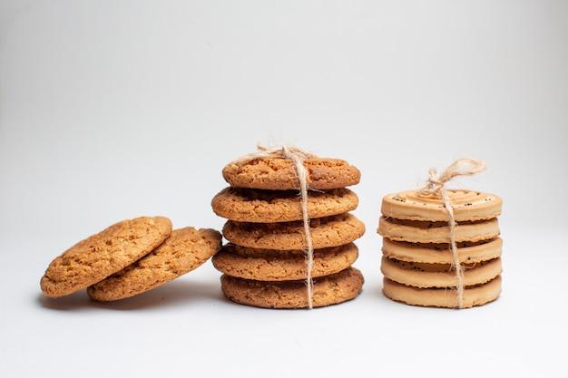 Vista frontal diferentes galletas dulces sobre fondo blanco.