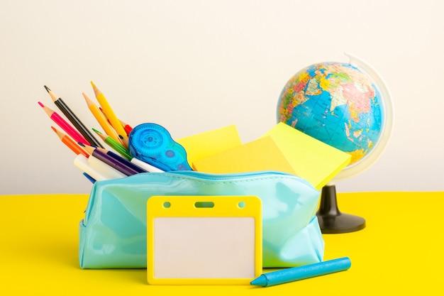 Vista frontal de diferentes lápices de colores dentro de la caja de bolígrafos azul con un pequeño globo en el escritorio amarillo