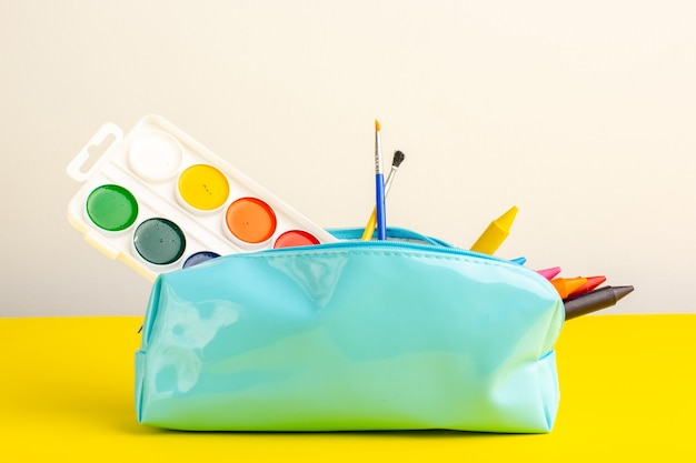 Vista frontal de diferentes lápices de colores y pinturas dentro de la caja de lápiz azul en el escritorio amarillo