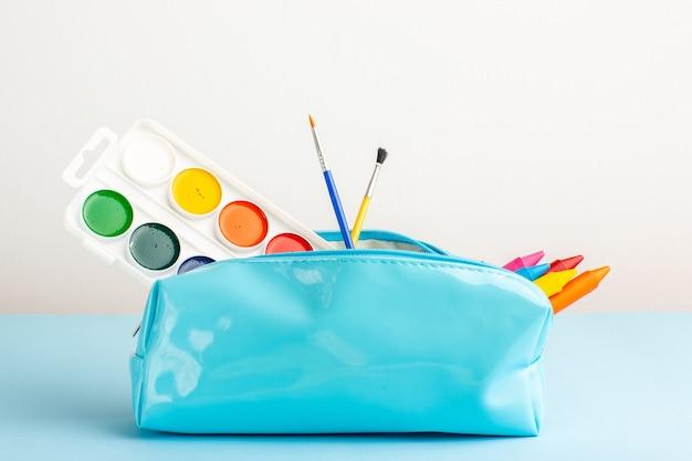 Vista frontal de diferentes lápices de colores y pinturas dentro de la caja de lápiz azul en el escritorio azul
