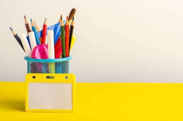 Vista frontal de diferentes lápices de colores con rotuladores en el escritorio amarillo claro