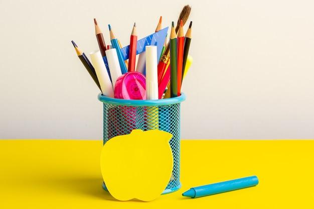 Vista frontal de diferentes lápices de colores con rotuladores en el escritorio amarillo