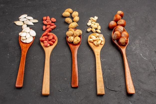 Vista frontal de diferentes nueces cacahuetes frescos y otras nueces en superficie oscura