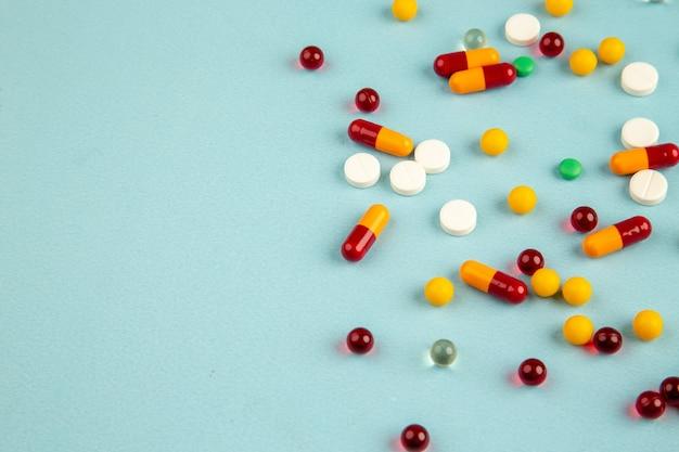 Vista frontal de diferentes píldoras de colores sobre la superficie azul color de laboratorio salud covid- virus hospitalario ciencia medicamentos pandémicos