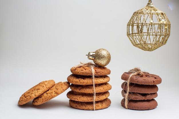 Vista frontal diferentes sabrosas galletas sobre fondo blanco.