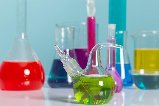 Vista frontal de diferentes soluciones coloridas dentro de matraces sobre la mesa