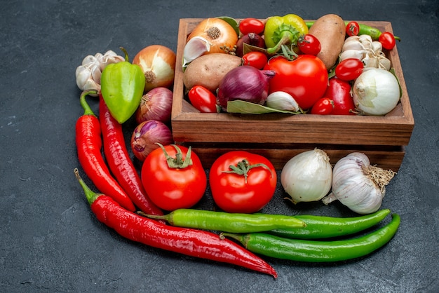 Vista frontal de diferentes verduras frescas en la mesa oscura ensalada de color maduro fresco