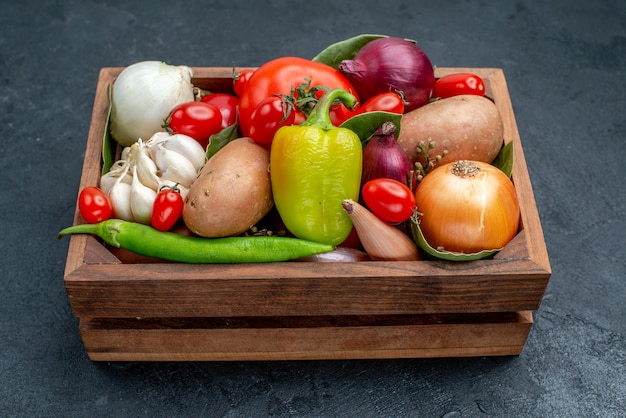 Vista frontal de diferentes verduras frescas en la mesa oscura ensalada fresca de verduras maduras