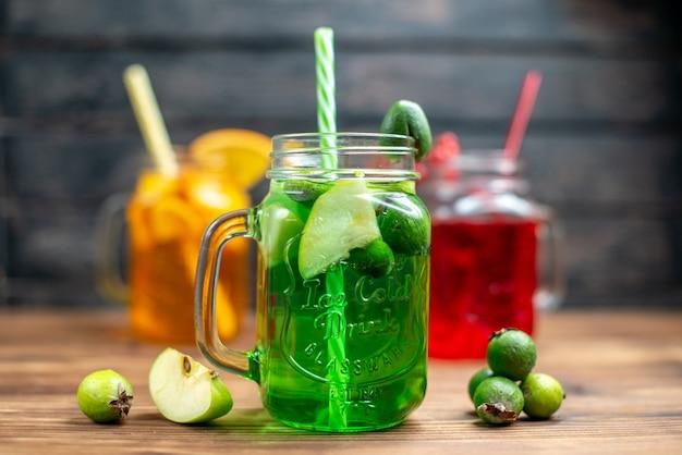 Vista frontal de diferentes zumos de frutas dentro de latas en el escritorio de madera marrón r