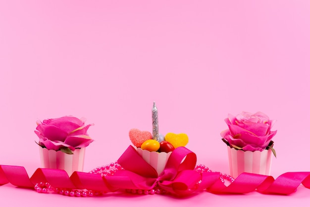 Una vista frontal diseñada en rosa, se presenta con flores y velas en rosa, color de belleza presente cumpleaños