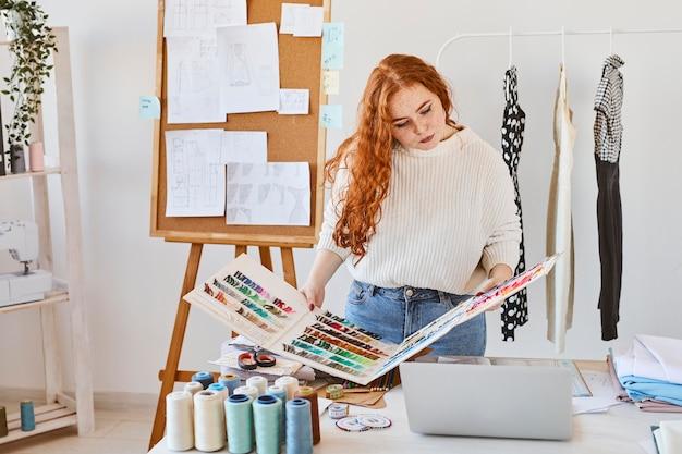 Vista frontal de la diseñadora de moda femenina en atelier con paleta de colores