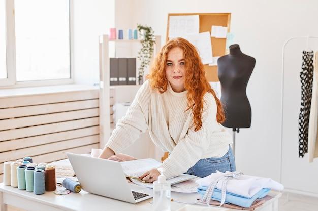 Vista frontal de la diseñadora de moda femenina que trabaja en el taller con un portátil