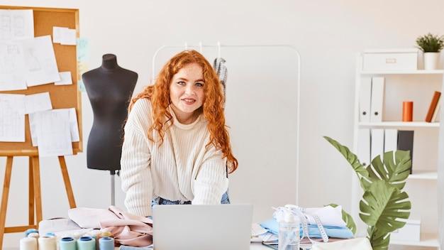 Vista frontal de la diseñadora de moda femenina sonriente que trabaja en el taller con el portátil