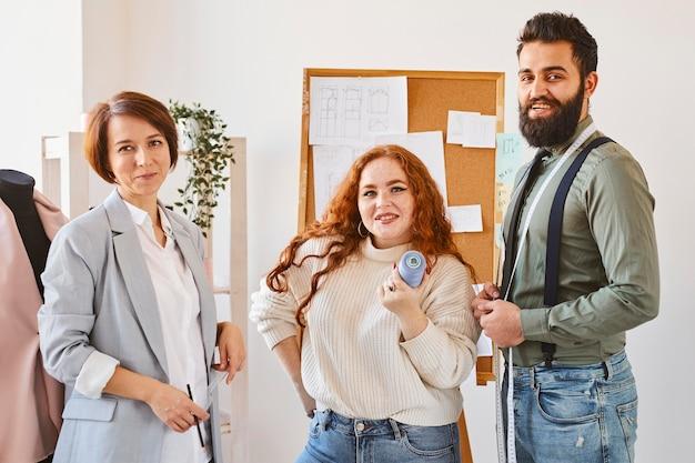 Vista frontal de los diseñadores de moda posando en su taller de negocios