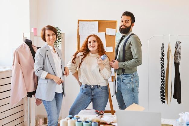 Vista frontal de diseñadores de moda sonrientes posando en su taller de negocios