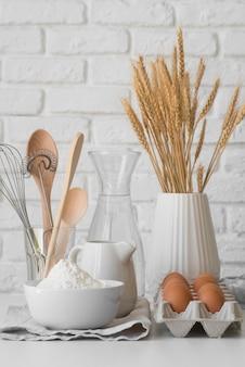 Vista frontal disposición de utensilios de cocina y huevos