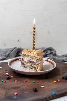 Vista frontal distante rebanada de pastel con vela dentro de la placa en el escritorio de madera y superficie luminosa