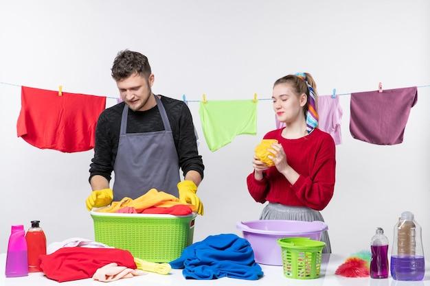 Vista frontal divertida pareja joven hombre sosteniendo canasta de lavandería y esposa sosteniendo una esponja de baño en la pared blanca