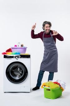 Vista frontal divertido hombre alegre de pie cerca de la cesta de lavandería lavadora sobre fondo blanco.