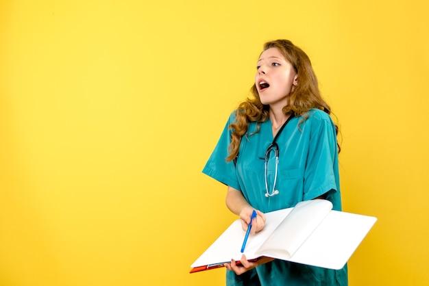 Vista frontal de la doctora con análisis sobre pared amarilla