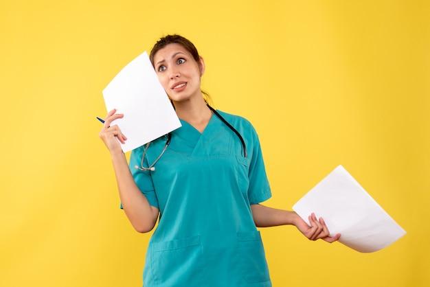 Vista frontal doctora en camisa médica con análisis de papel sobre fondo amarillo
