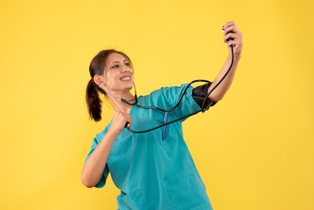 Vista frontal doctora en camisa médica comprobando su presión sobre fondo amarillo