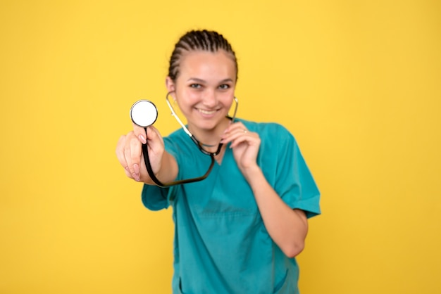 Vista frontal de la doctora en camisa médica con estetoscopio en pared amarilla