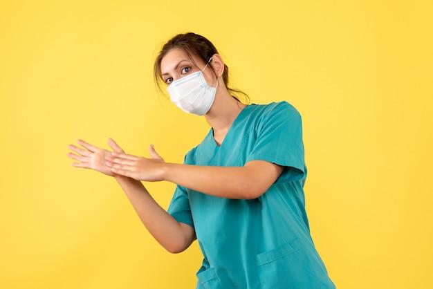 Vista frontal doctora en camisa médica y con máscara estéril sobre fondo amarillo