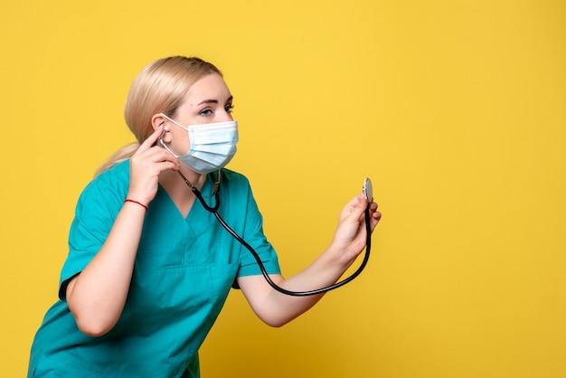 Vista frontal doctora en camisa médica y máscara con estetoscopio, enfermero de salud del hospital médico covid-19 pandemia